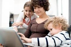 使用膝上型计算机的妇女和孩子 免版税库存照片