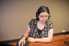 使用膝上型计算机的妇女和谈话在耳机 库存图片