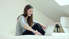 使用膝上型计算机的妇女在家坐床 免版税库存照片