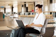 使用膝上型计算机的妇女在机场 免版税库存照片