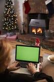 使用膝上型计算机的妇女在装饰的屋子里为圣诞节 库存照片