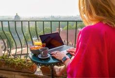 使用膝上型计算机的妇女在阳台的早餐期间 图库摄影