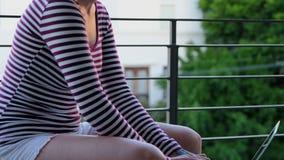 使用膝上型计算机的妇女在阳台4k 影视素材