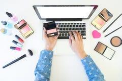 使用膝上型计算机的妇女顶视图为搜寻化妆informatio 库存图片