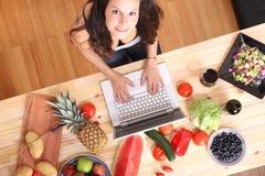 使用膝上型计算机的妇女,当烹调时 免版税库存图片