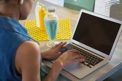 使用膝上型计算机的妇女,当食用奶昔在餐馆时 免版税库存照片