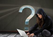 使用膝上型计算机的妇女黑客在有问号的一间屋子里对此 库存照片
