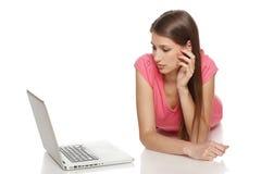 使用膝上型计算机的妇女说谎在地板上 免版税库存照片