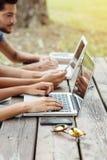 使用膝上型计算机的学生在公园 免版税库存照片