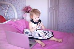 使用膝上型计算机的小女孩孩子坐床 免版税库存图片