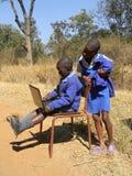 使用膝上型计算机的小学孩子户外 免版税库存照片