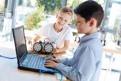 使用膝上型计算机的小男孩在机器人学车间期间 库存照片