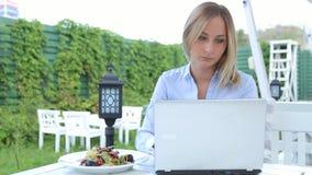 使用膝上型计算机的少妇和吃坐的沙拉在咖啡馆在城市 股票录像