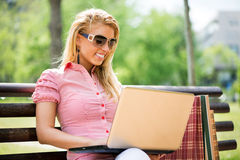 使用膝上型计算机的少妇在公园 库存照片