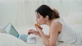 使用膝上型计算机的少妇在家说谎在白色床上的早餐期间 键入在个人计算机和吃新月形面包的深色的女孩 影视素材