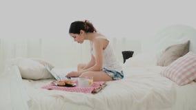 使用膝上型计算机的少妇在早餐期间在家坐白色床 深色的在个人计算机的女孩键入的消息,聊天 影视素材