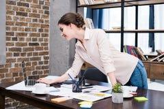 使用膝上型计算机的少妇在有纸和办公用品的书桌 库存图片