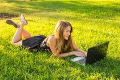 使用膝上型计算机的少妇在说谎在绿草的公园 业余时间活动概念 免版税库存照片