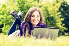 使用膝上型计算机的少妇在说谎在绿草的公园 免版税图库摄影