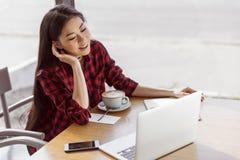 使用膝上型计算机的少妇,当喝热奶咖啡在咖啡休息时 免版税库存照片