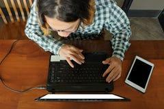 使用膝上型计算机的工作者鸟瞰图为他的工作在书桌在办公室 免版税库存图片