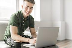 使用膝上型计算机的帅哥在家坐长沙发 库存照片