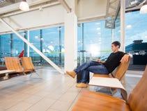 使用膝上型计算机的年轻人在机场大厅 库存图片