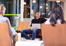 使用膝上型计算机的年轻人在机场等待的大厅 库存图片