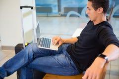使用膝上型计算机的年轻人,当等待飞行时 图库摄影