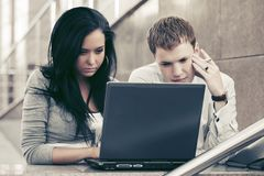 使用膝上型计算机的年轻企业夫妇在办公楼 免版税库存照片