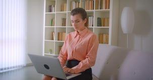 使用膝上型计算机的年轻可爱的女实业家特写镜头画象坐长沙发在公寓户内 影视素材