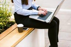 使用膝上型计算机的年轻女商人室外,当喝咖啡时 免版税库存照片