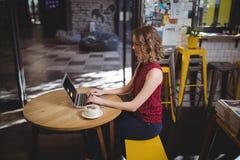 使用膝上型计算机的年轻女性顾客侧视图,当坐在桌时 库存图片