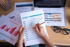 使用膝上型计算机的年轻职业妇女顶视图和读年终报告文件在工作 企业服务台她的妇女工作 免版税图库摄影