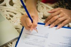 使用膝上型计算机的年轻职业妇女顶视图和读年终报告文件在工作 企业服务台她的妇女工作 免版税库存图片