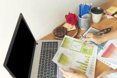 使用膝上型计算机的年轻职业妇女顶视图和读年终报告文件在工作 企业服务台她的妇女工作 库存照片