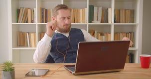 使用膝上型计算机的年轻被集中的白种人商人特写镜头画象在震动在办公室户内与 影视素材
