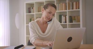 使用膝上型计算机的年长白种人深色的女实业家特写镜头画象和有电话在办公室 影视素材