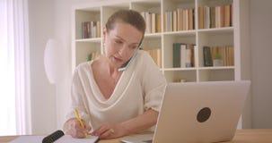 使用膝上型计算机的年长白种人深色的女实业家特写镜头画象和有采取笔记的电话  股票录像
