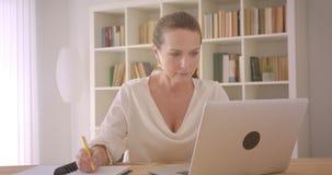 使用膝上型计算机的年长白种人深色的女实业家特写镜头画象和采取笔记在办公室户内 股票视频