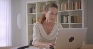 使用膝上型计算机的年长白种人深色的女实业家特写镜头画象在办公室户内 股票录像