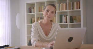 使用膝上型计算机的年长白种人深色的女实业家特写镜头画象看快乐地微笑的照相机  股票录像