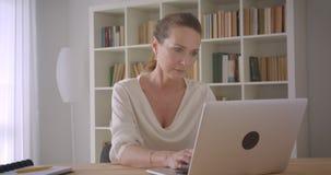 使用膝上型计算机的年长白种人深色的女实业家特写镜头画象看照相机在办公室户内 股票录像