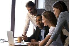 使用膝上型计算机的微笑的不同的队谈论网上项目在m 库存图片