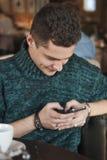 使用膝上型计算机的微笑的人在咖啡馆 图库摄影