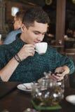 使用膝上型计算机的微笑的人在咖啡馆 库存照片