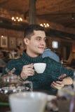使用膝上型计算机的微笑的人在咖啡馆 免版税库存照片