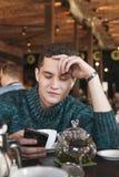 使用膝上型计算机的微笑的人在咖啡馆 免版税库存图片