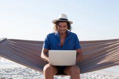 使用膝上型计算机的微笑的人,当坐吊床在海滩时 免版税库存照片