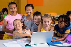 使用膝上型计算机的微笑的多种族孩子 免版税库存照片